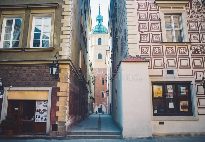 Old ancient polish architecture. Colorful houses as a part of center of the Warsaw. Beautiful church on narrow street royalty free stock photo
