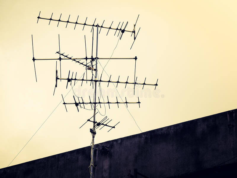 Old antenna with sky background. Vintage look filter, Old antenna with sky background. Silhouetted image for commutation concept stock photography