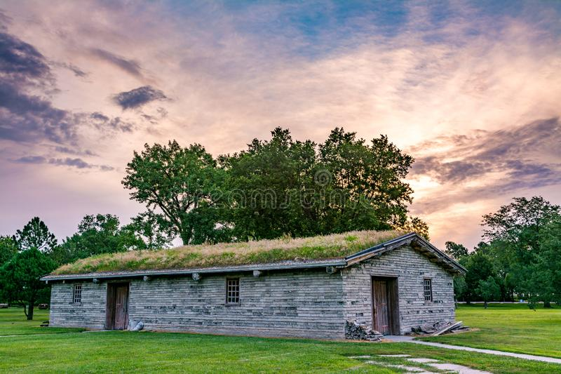 Old antique building in Nebraska with a sod roof surrounded by t. Long building made from mud bricks with a sod roof and sunrise royalty free stock photo