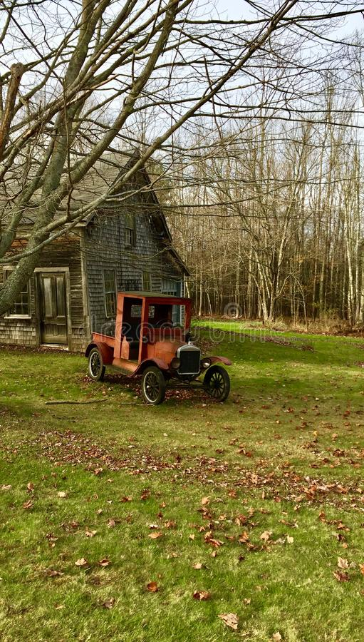 Old antique car and a shack. Old vintage antique car model in front of an old shack in the fall in Maine stock image