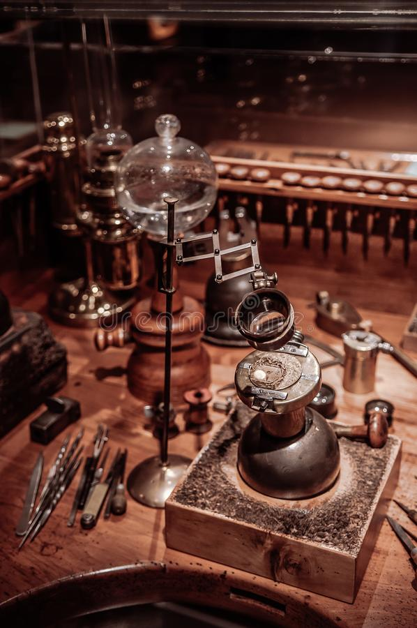 Old antique clockmaker table with tools. SEP 26, 2013 Neuchatel, Switzerland - old vintage antique Old antique wooden clockmaker table with tools at royalty free stock photo