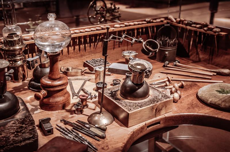 Old antique clockmaker table with tools. SEP 26, 2013 Neuchatel, Switzerland - old vintage antique Old antique wooden clockmaker table with tools at royalty free stock photos