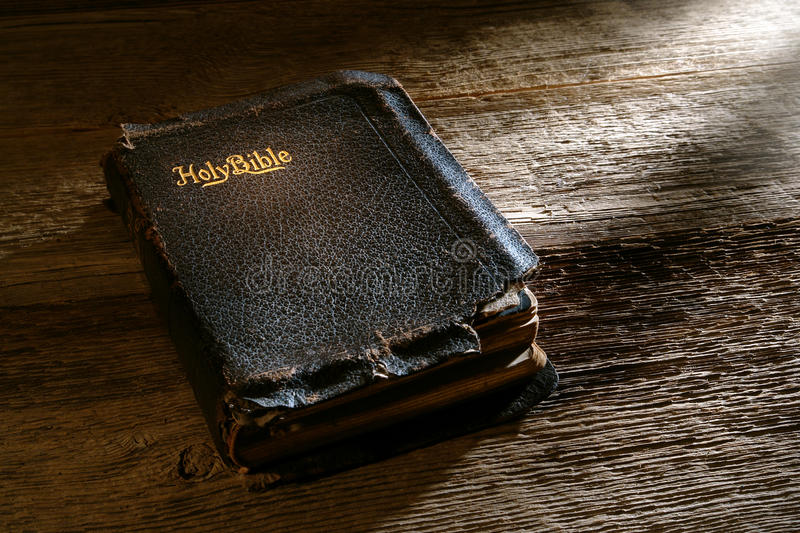 Old Antique Damaged Holy Bible Sacred Book on Wood. Old antique and damaged holy bible sacred religious book on weathered wood bench in a vintage church royalty free stock image