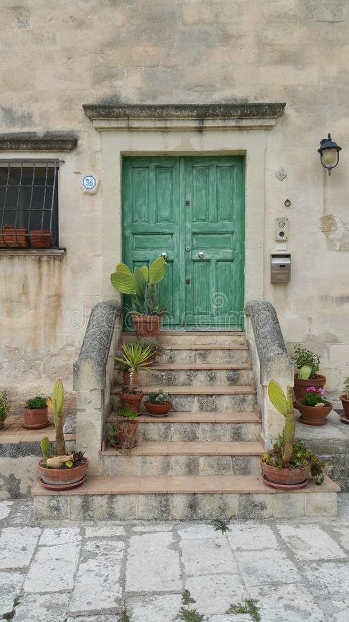 Old antique front door with steps. Old green front door with steps in the south of Italy royalty free stock images