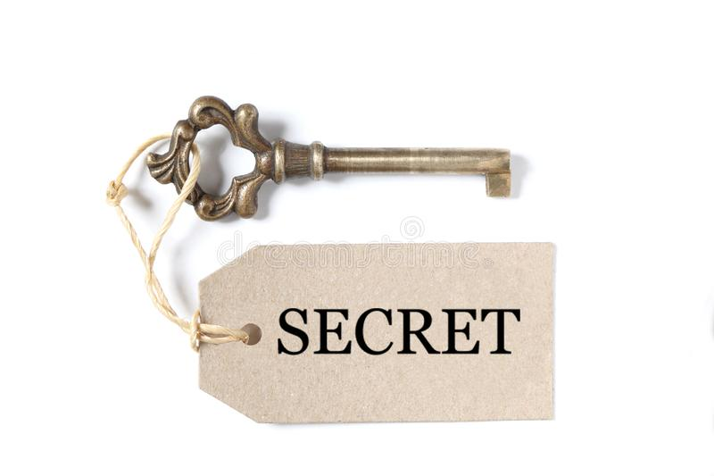 Old antique key with a label and the word secret isolated on white background with copy space. Old antique key with a label and the word secret on white stock photo