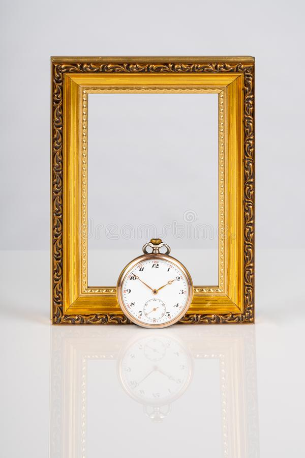 Old antique mechanical golden steel pocket watch in front of an empty wooden gold frame isolated on white background. royalty free stock photos