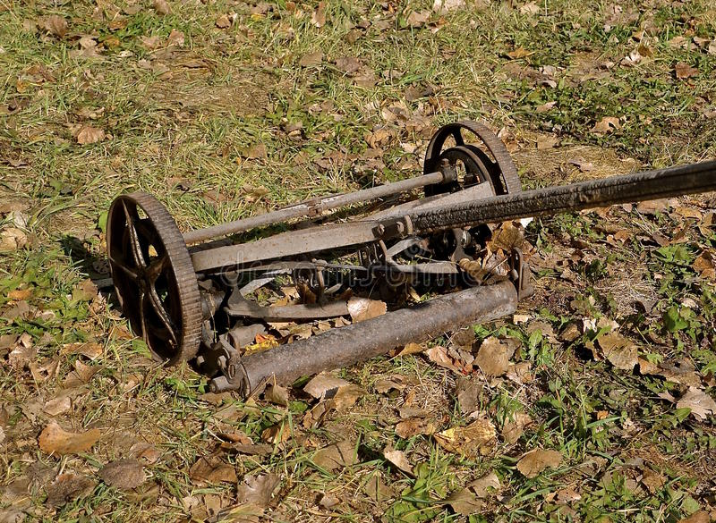 Old antique push mower. A rusty antique push mower with a wooden handle royalty free stock photos