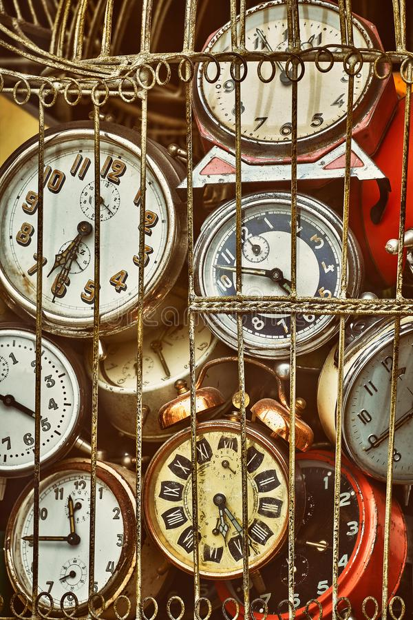 Old antique clocks in iron cage collection. Old antique retro clocks in iron cage. Collection of vintage alarm clock. Lost time concept royalty free stock photo