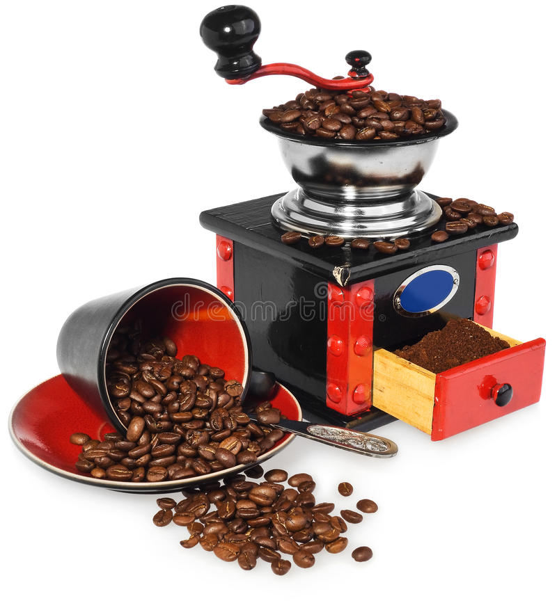 Old antique wooden black and red coffee grinder, cup, silver spoon and spilled coffee beans. royalty free stock image