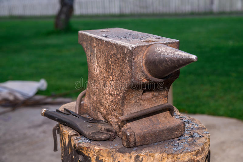 The old anvil is on the stump. Surrounded by a beautiful lawn, s stock photo