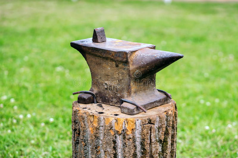 The old anvil is on the stump. stock images