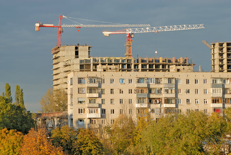 Old Apartment House Against Construction Crane Stock Photo
