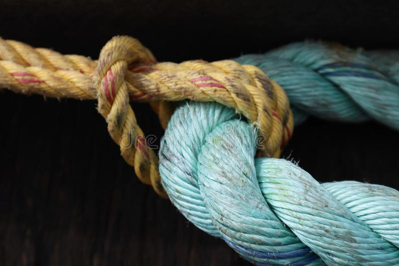 Old Yellow and Aqua Blue Rope Tied in Knot royalty free stock image