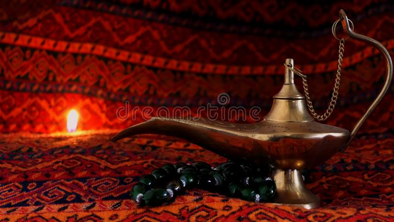 Old Arabic lamp with smoke, magical lamp closeup over dark background. Arabic objects over Warm fabric. Islamic Ramadan elements royalty free stock images