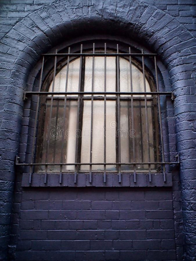 Old arched window in a black brick wall with heavy metal bars royalty free stock photos
