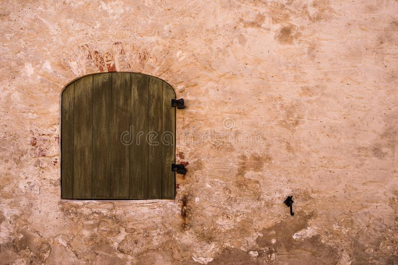 Old arched Window closed by wooden shutters and red wall royalty free stock image