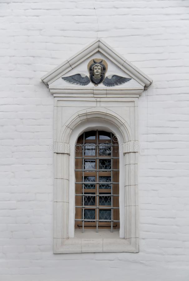 Old arched window with metall lattice and relief on a white brick wall of christian church.  stock image