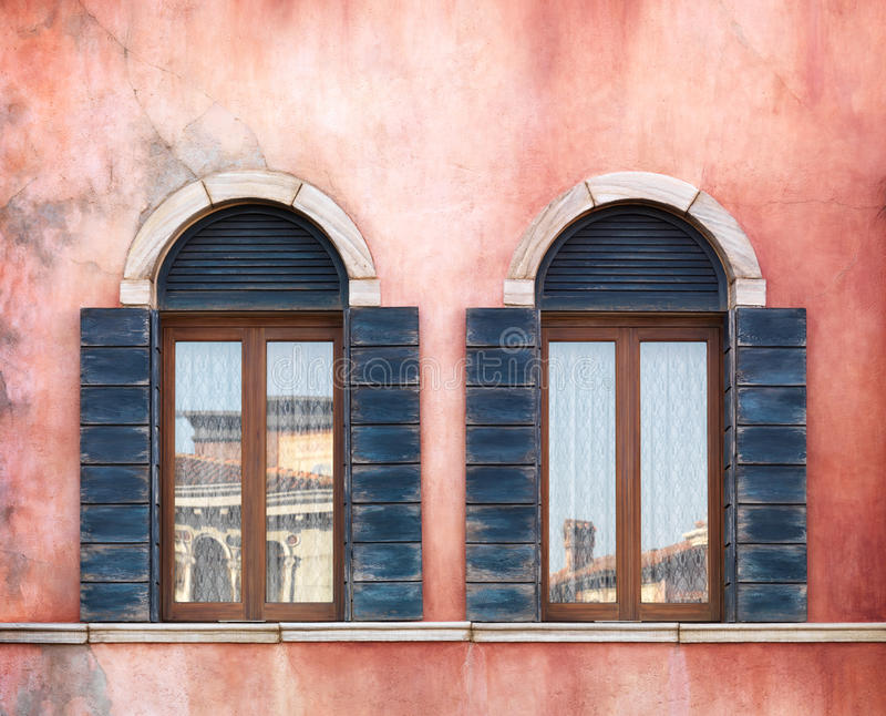 Old arched windows. Wall with two old arched windows with shutters, rustic texture royalty free stock photo
