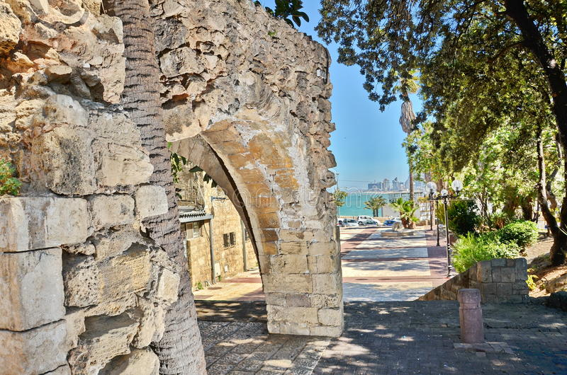 Old arches in Jaffa, Israel. Old stone arches with the The Tel Aviv sky line background in Jaffa, Israel royalty free stock images