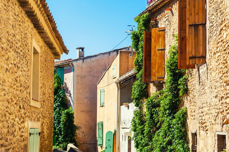 Old architecture in Valensole, Provence, France. Stone houses and windows with wooden shutters royalty free stock image