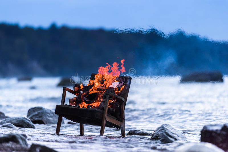 Old armchair in fire stock images