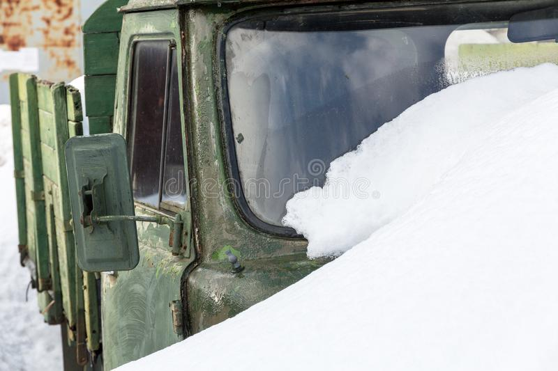 Old army car green covered with snow stock photography