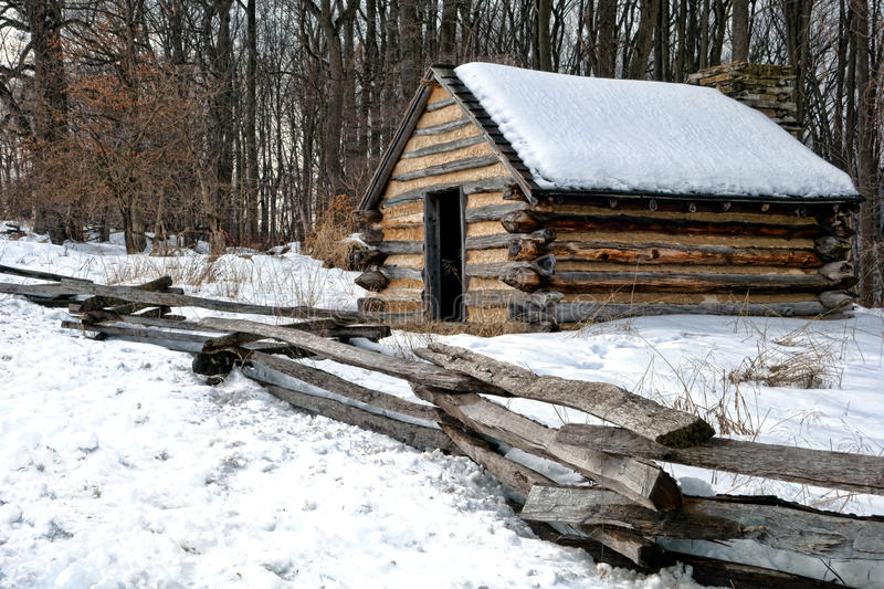 Old Army Wood Cabin at Valley Forge National Park. American Revolutionary War soldier housing wood cabin with wooden fence in an encampment in winter snow near stock image