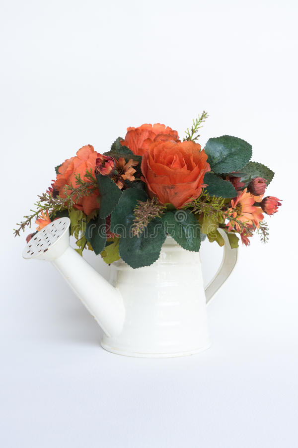 Old artificial flowers in rusted white waterpot on white royalty free stock photos