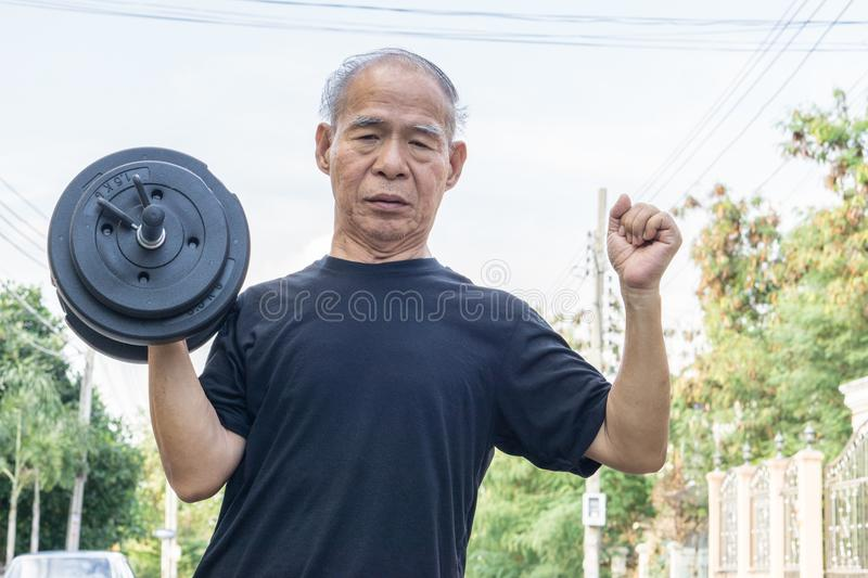 Old asia man with dumbbells. Person doing exercise outdoor. royalty free stock image