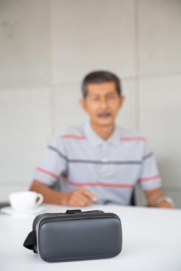 Old Asian man interest new technology VR royalty free stock photo