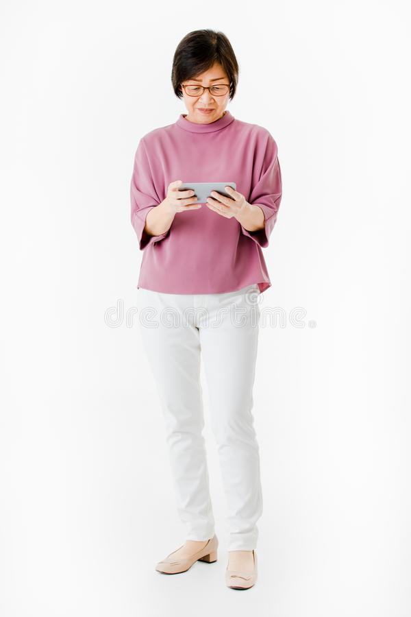 Old Asian woman looking to screen of smartphone and look like feel confuse and worry. Concept for technology learning of older.  stock photography