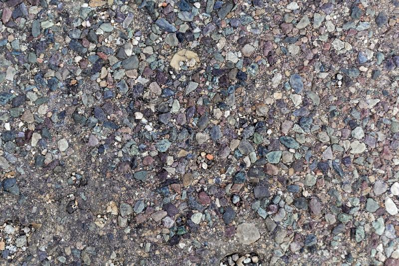 Old asphalt street pavement. With different colored stones as additive stock photo
