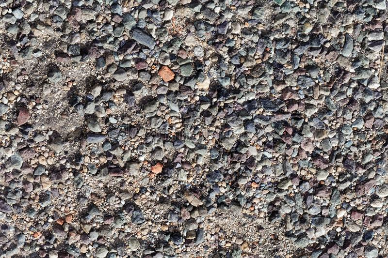 Old asphalt street pavement. With different colored stones as additive stock image