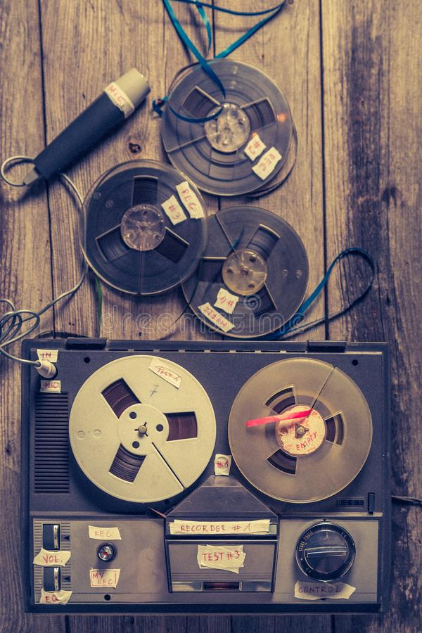 Old audio reel recorder with roll of tape and microphone. On old table royalty free stock image