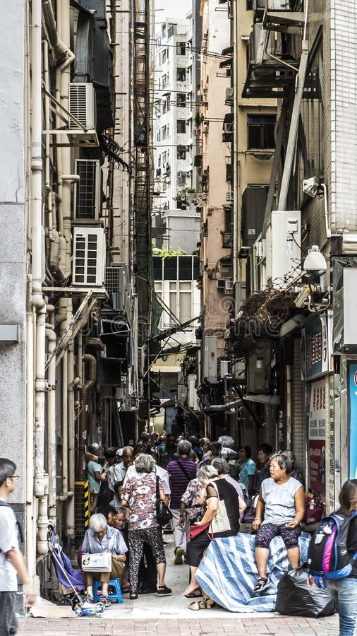 Old people gather in the shade under apartment buildings in Hong Kong royalty free stock photography