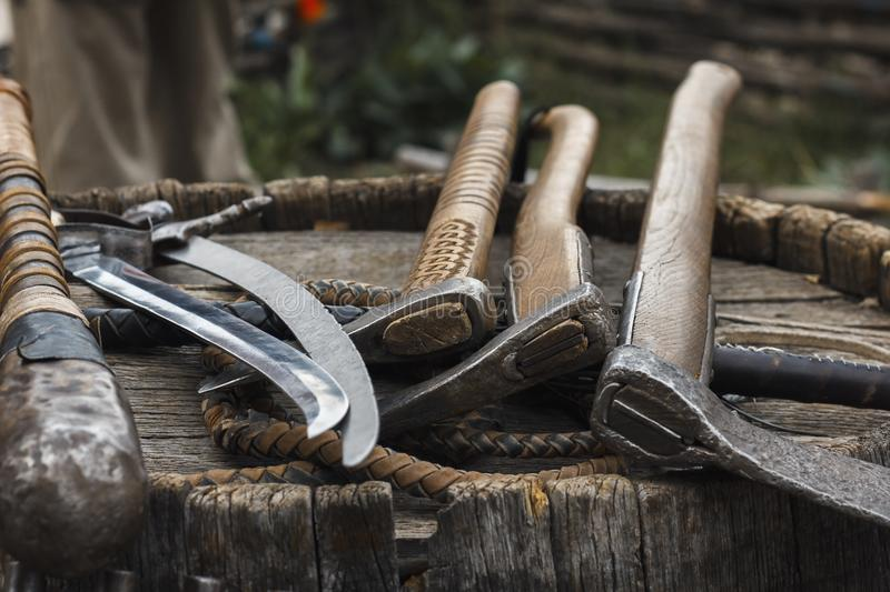 Axes and sabers on the barrel. Old axes and sabers on the wooden barrel stock images