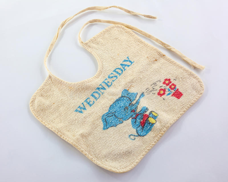Old baby bib with ties. Decorated with text ' wednesday' in uppercase blue letters and below it an elephant watering flowers through its trunk, pale background stock photography