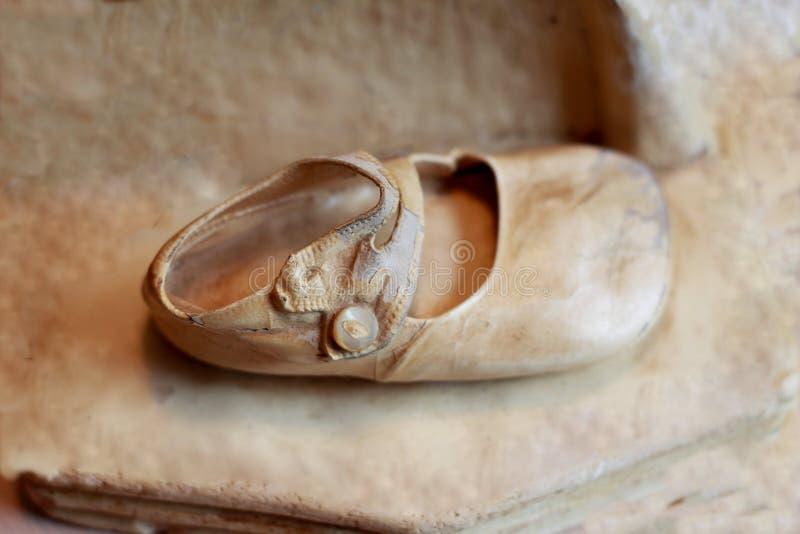 Old baby shoe. Ivory coating stock images
