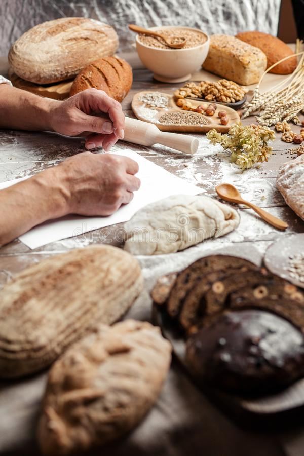 Old Baker writing down old-time recipe in bakery notebook surrounded by bread royalty free stock image