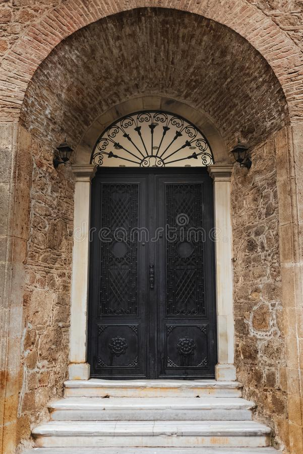 Old balck door in brown wall. Vertical color photography.  stock images
