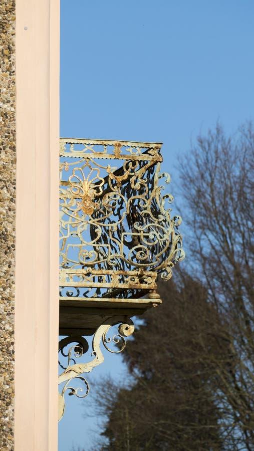Old balcony railing, with filigree ornaments, and face gold. Old balcony railing, with filigree ornaments, and face, and a shell in gold royalty free stock photo