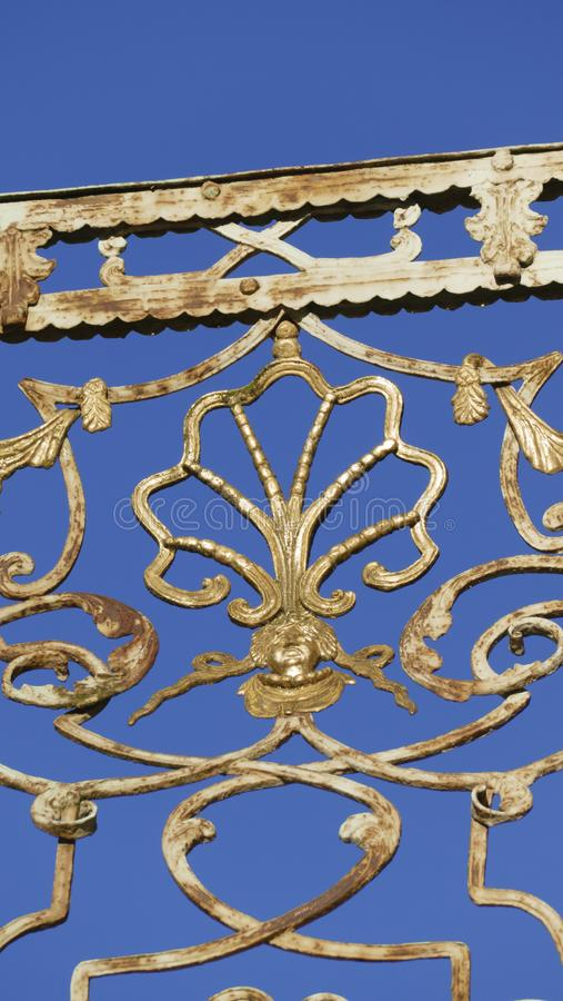 Old balcony railing, with filigree ornaments, and face gold. Old balcony railing, with filigree ornaments, and face, and a shell in gold stock image