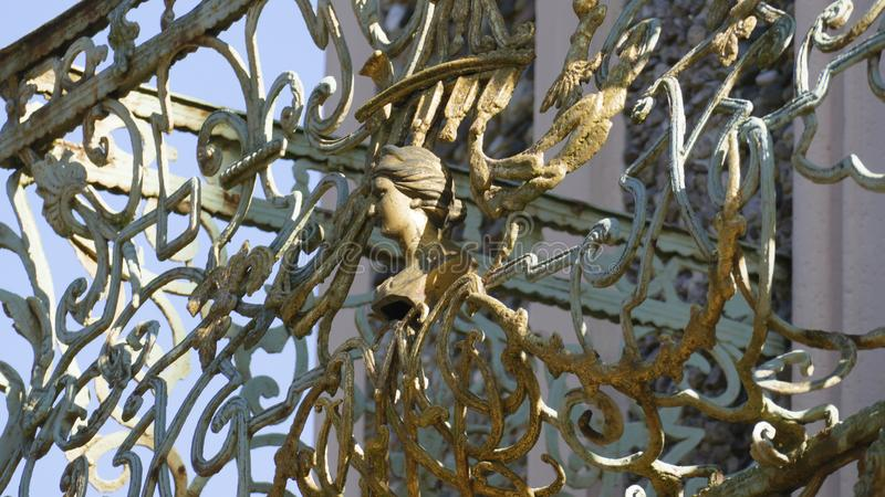 Old balcony railing, with filigree ornaments, and face gold. Old balcony railing, with filigree ornaments, and face, and a shell in gold royalty free stock image