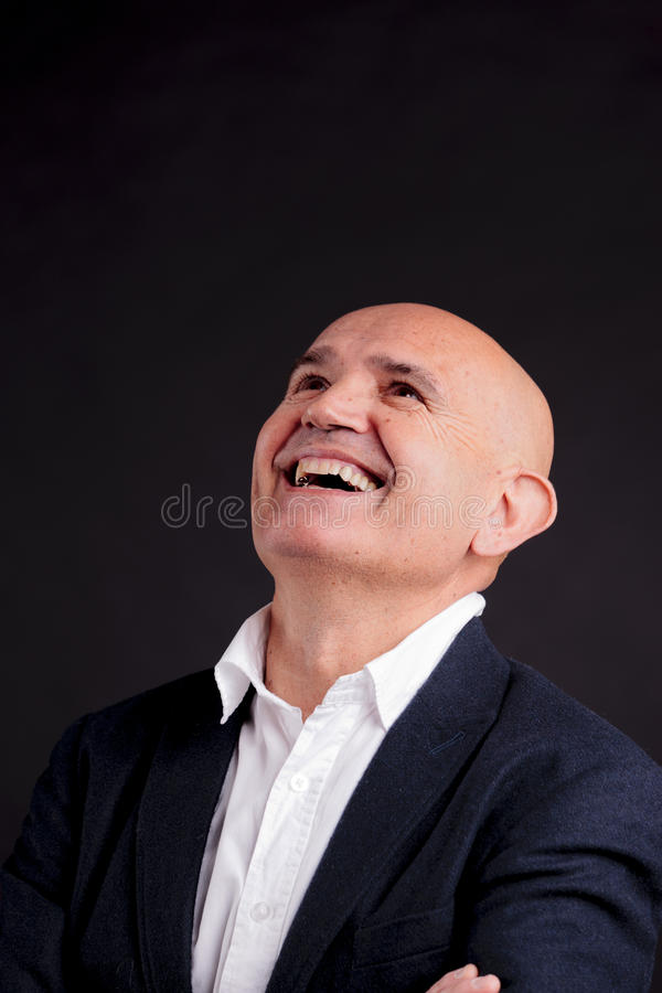 Old bald businessman. Old bald self-confident businessman on a dark background royalty free stock photography
