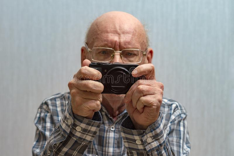 An old bald man with glasses looks at the footage on the camera. Copy spac. E royalty free stock image