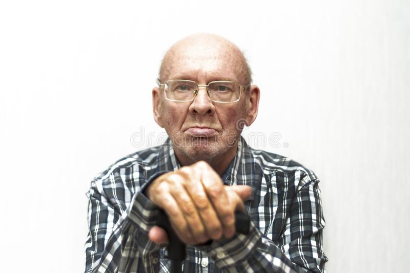 Old bald man in glasses shows middle finger. stock photos