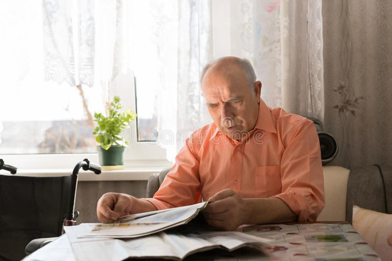 Old Bald Man Reading News Updates on Tabloid. Close up Old Bald Man Reading News Updates on Tabloid While Sitting at the Living Room Near the Window royalty free stock photo