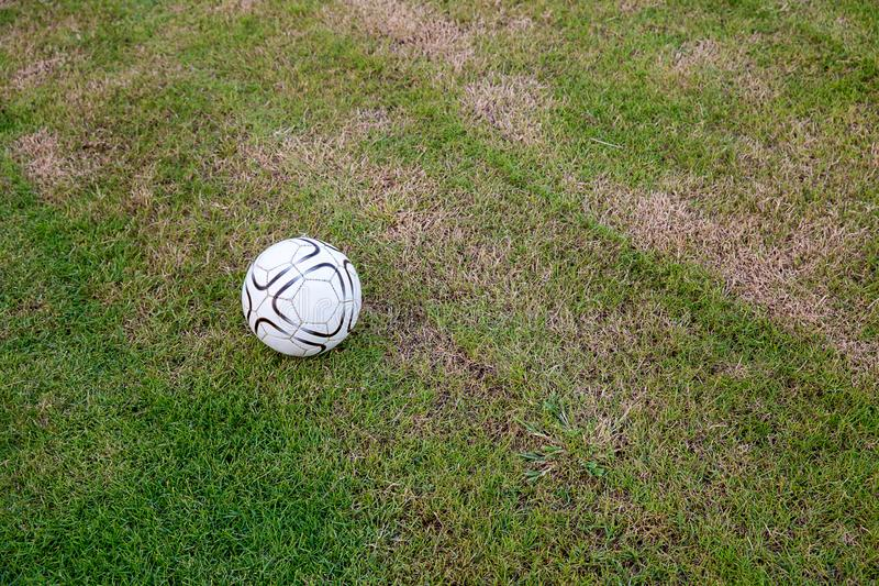 Old ball on the artificial turf at the stadium. view of green striped football royalty free stock images