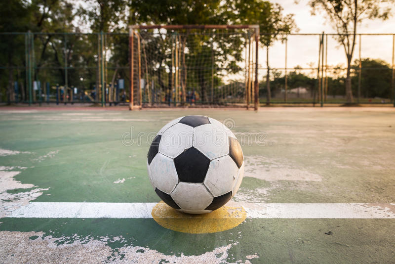 Old ball at kick off point in court. Old football at kick off point in court royalty free stock photos