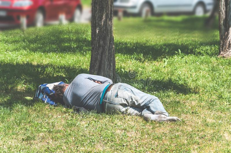 Old barefoot homeless or refugee man sleeping on the grass in the city park using his travel bag as pillow, social documentary str royalty free stock photography